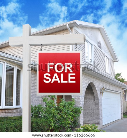 A home is advertising a for sale sign on a wooden sign post in red. Use it for a housing market concept. - stock photo