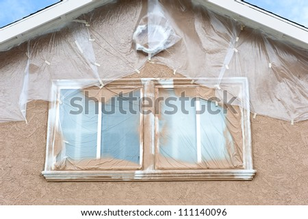 A home is being repainted and is painstakenly masked with plastic sheeting to protect areas from paint overspray during a remodeling project. - stock photo