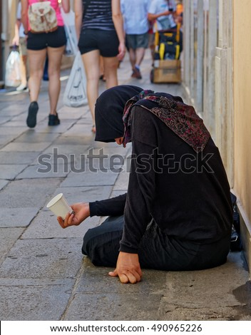 A homeless female beggar is begging on the street in Venice, Italy
