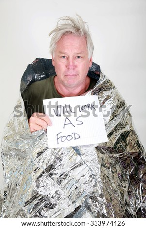 A homeless man in a silver emergency survival space blanked with a will work for food sign.  In Black and White - stock photo