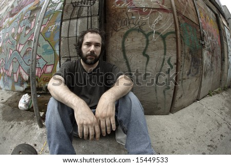 A homeless man on the city streets, filled with anxiety and hopelessness.  Shot with fish-eye lens and de-saturated. - stock photo