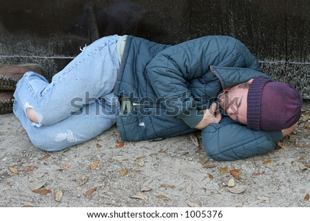 A homeless man sleeping on the ground beside a dumpster. - stock photo