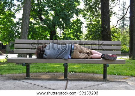 A homeless person takes a nap on a bench in a public park. - stock photo