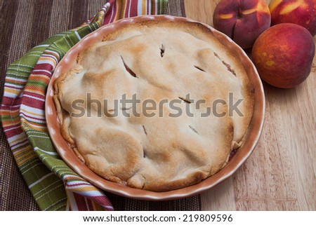 A homemade peach pie rests on a countertop fresh out of the oven. - stock photo