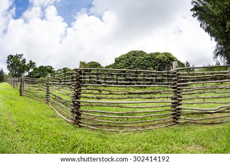 A homemade wooden ranch fence made from tree branches lined the outskirts of a ranch in the highlands of Hawaii.   - stock photo