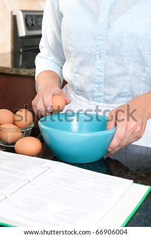 A homemaker cracks an egg into a mixing bowl while following the instructions of a cookbook. - stock photo