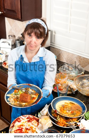 A homemaker gets ready to wash dishes with little enthusiasm.