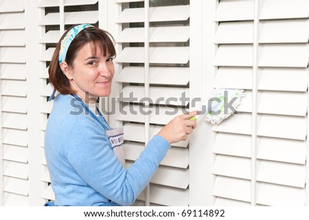 A homemaker uses a hand held duster to clean some wooden window shutters - stock photo