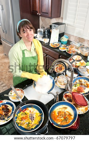 A homemaker washing a bunch of dirty, filthy dishes in a domestic kitchen. - stock photo