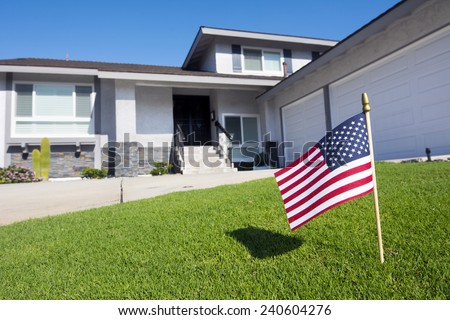 A homeowner displays an American flag in their yard during a patriotic holiday - stock photo