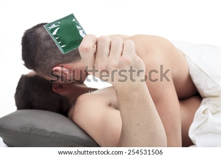 A homosexual couple onder a bed in studio white on studio. - stock photo