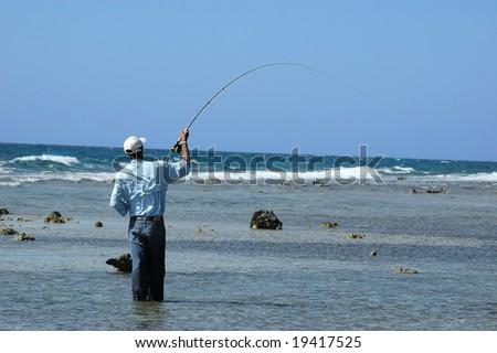 A honduran guide plays a bonefish on the flats on the island of Roatan. Lumps of coral emerge from the flats, and in the background the open sea. - stock photo