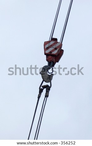 A hook from a crane hanging from the blue sky