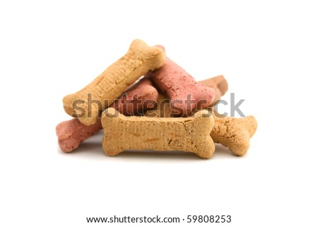 A horizontal color photograph of a pile of dog biscuits over a white background. - stock photo