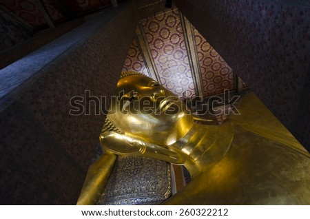 A horizontal image of the reclining gold Buddha at Wat Pho in Bangkok Thailand - stock photo