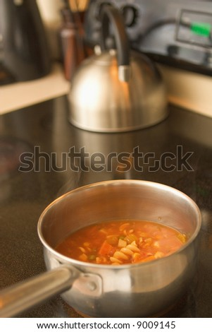 A horizontal view of vegetable soup cooking in a pot on a glass top stove. - stock photo
