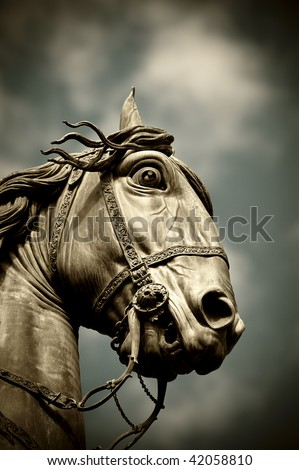 A horse head statue isolated over a blue sky - stock photo
