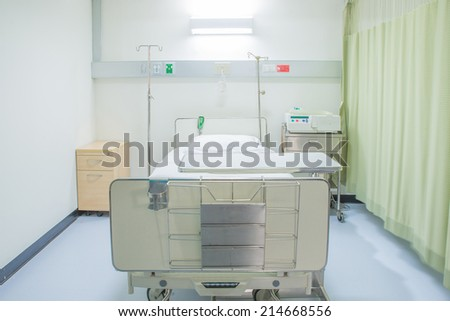 A hospital room with bed and chair - stock photo