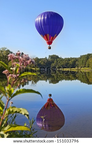 A hot air balloon rises into a blue sky over a clear pond with a sharp reflection. - stock photo