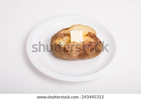A hot baked potato, cut open and buttered on a white plate and background - stock photo