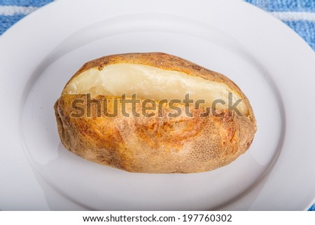 A hot baked potato on a white plate - stock photo