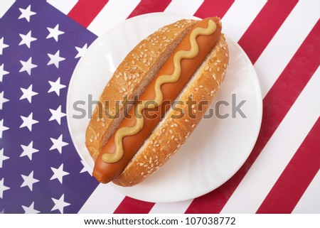 A Hot Dog in a bun with yellow mustard on a plate on American flag - stock photo