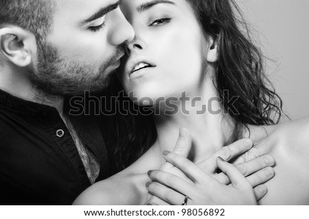 a hot man is kissing his  beautiful young woman - stock photo