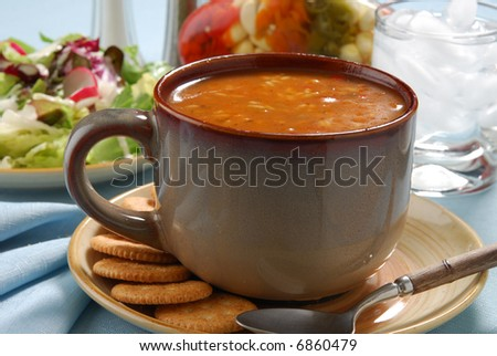 A hot meal of chicken gumbo soup and salad - stock photo