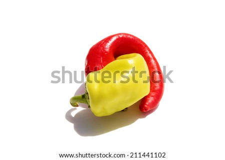 A Hot Red and Yellow Pepper entangle in an erotic embrace isolated on white with room for your text. Peppers are known as Aphrodisiacs around the world by various people and cultures.  - stock photo