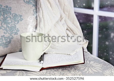 A hot relaxing cup of coffee or cocoa with an open book sitting on a comfortable chair with blanket. Extreme shallow depth of field.  - stock photo