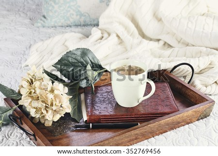 A hot relaxing cup of coffee with a book and flowers in a serving tray sitting on a comfortable bed with blanket. Extreme shallow depth of field.  - stock photo