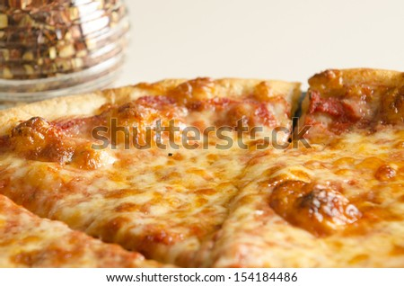 A hot, tasty, cheese pizza on a counter top with a jar of red pepper flakes in the background.  - stock photo