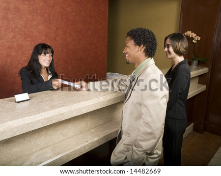 A hotel employee cheerfully welcomes guests.