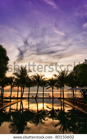 A hotel infinity pool in Thailand at sunrise with a paradise backdrop of palm trees and ocean. - stock photo