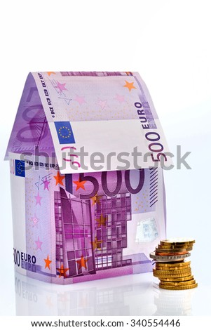 a house built with money seem ? on a white background. building savings, house building and home buying. - stock photo