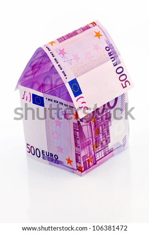a house built with money seem �¢â���¬ on a white background. savings, house building and home buying.