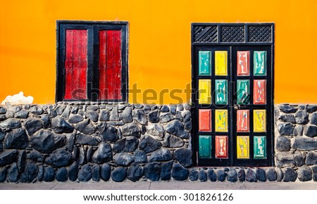 A house front with a radiant orange facade, colorful, old, partially peeled door in yellow, green and red and a bright red window shutters - stock photo