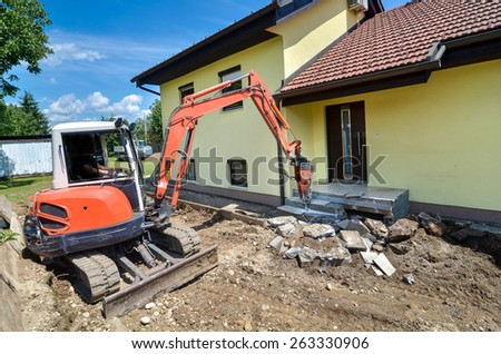 A house is being foreclosed and demolished with a crusher - stock photo