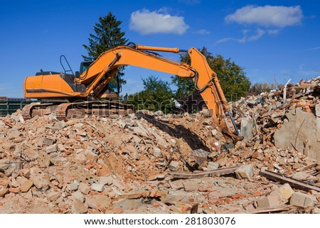 a house is demolished. excavator on the construction site. after demolition of new residential space will be created - stock photo