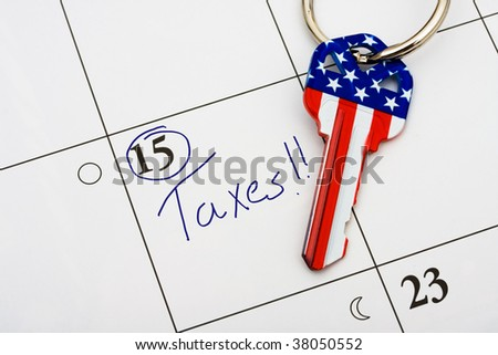 A house key on a calendar background, paying your taxes on time - stock photo