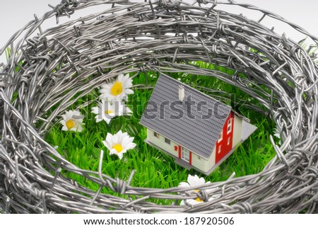 A house on a green meadow surrounded by barbed wire. - stock photo