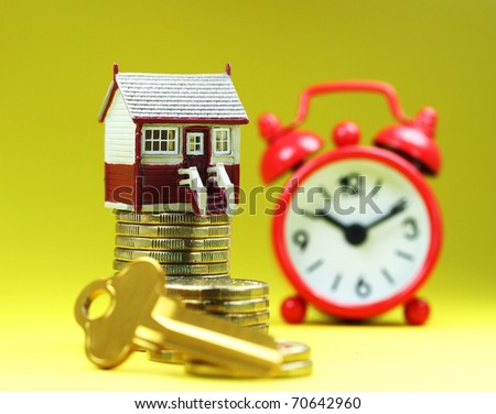 A house placed on a pile of gold coins with a golden key in front and a red alarm clock behind, asking the question is it time to buy that dream house? - stock photo