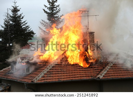 A house roof on fire and smoke. - stock photo