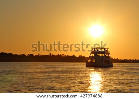 A houseboat cruises the Zambezi River, the border between Zimbabwe and Zambia, Africa, at sunset as the tourists on board enjoy sundowner cocktails. Sunset Cruise. Focus on boat. - stock photo