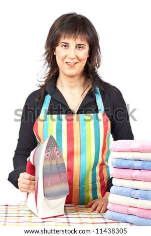 A housewife in apron holding a electric iron close to towels stacked - stock photo