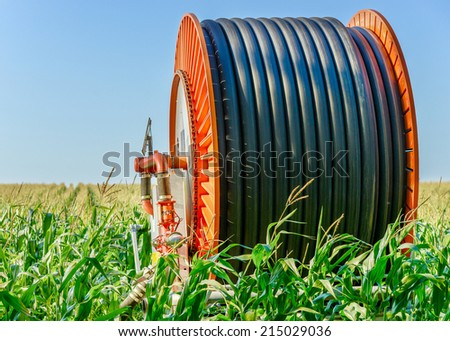 A huge coil of black hose with orange sides in the middle of the open field - stock photo
