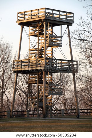 A huge fire watch tower or ranger station overlooks hundreds of acres of forest. - stock photo