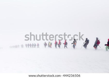 A huge group of people descends from the Elbrus in the fog. The concept of climbing the mountain in a snow storm