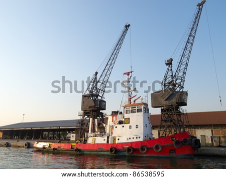 A huge orange tugboat in a harbor