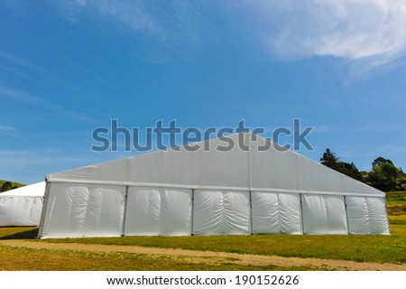 A huge tent in a grass field under sunny sky - stock photo